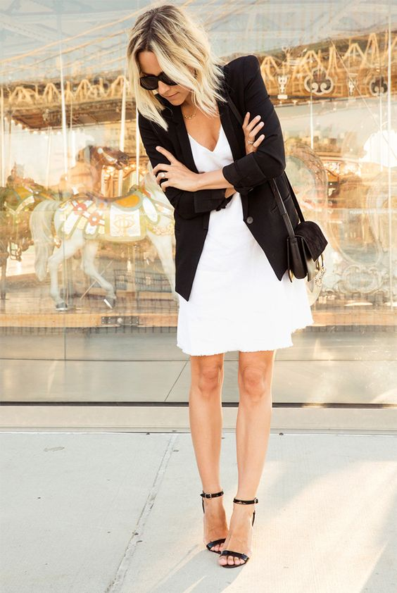 a white over the knee dress, a black blazer, black ankle strap shoes and a black bag
