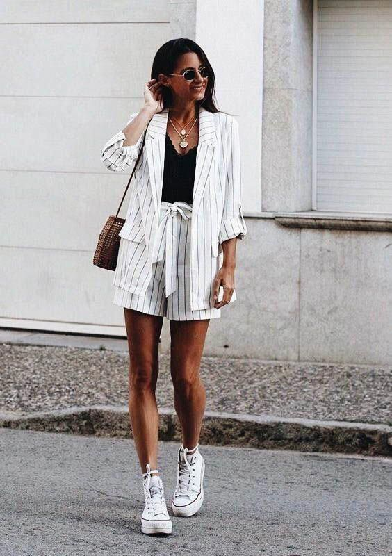 a white thin stripe oversized suit with shorts, a black top, white sneakers and a comfy bag for a boho feel
