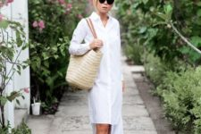 16 an asymmetrical white shirtdress, black slippers and a straw bag for an effortlessly chic look