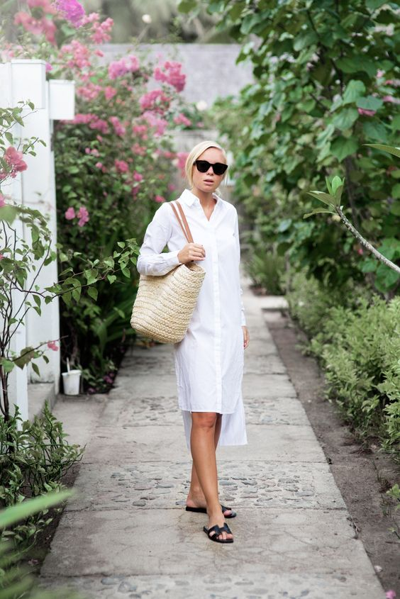 an asymmetrical white shirtdress, black slippers and a straw bag for an effortlessly chic look