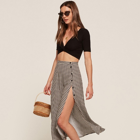 With black crop top and straw bag