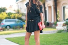 With black mini dress, belt and red clutch
