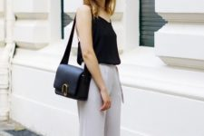 With black shirt, black leather bag and sandals