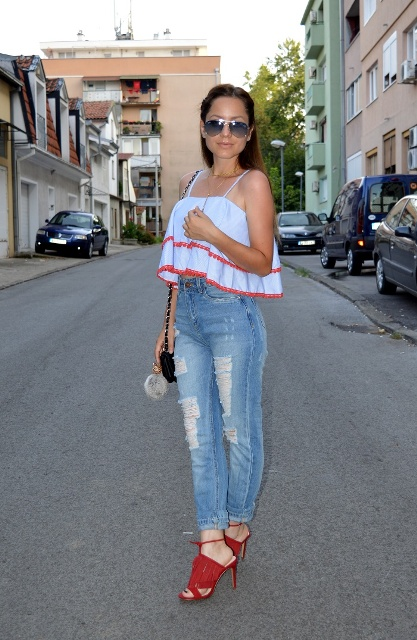 With distressed jeans, black bag and red heels