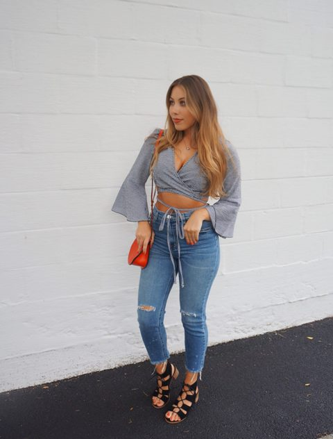 With distressed jeans, red bag and lace up sandals