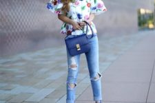 With floral blouse, distressed jeans and navy blue bag