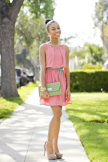 With green clutch and beige high heels