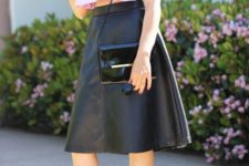 With leather skirt, black leather bag and high heels