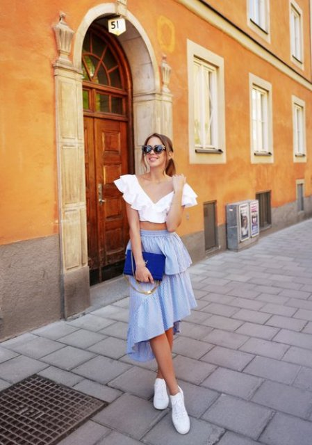 With light blue ruffled skirt, cobalt blue clutch and white sneakers