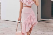 With pale pink ruffled skirt, pumps and chain strap bag