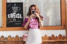 With pink one shoulder shirt and light pink bag