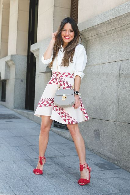 With white button down shirt, printed skirt and gray bag