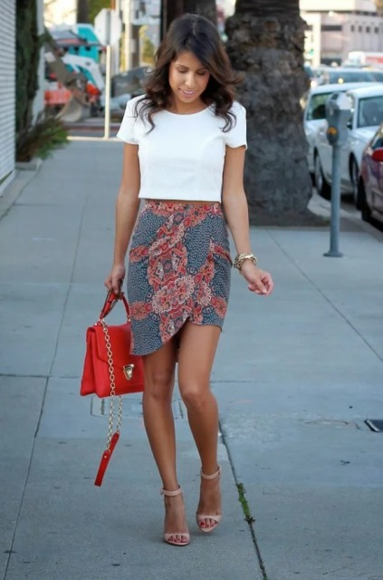 With white crop shirt, red bag and beige sandals