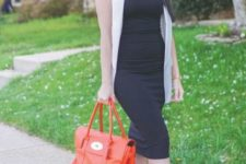 With white long vest, red bag and black high heels