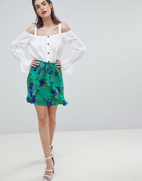 With white off the shoulder blouse and white high heels