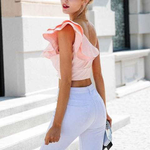 With white skinny pants and clutch