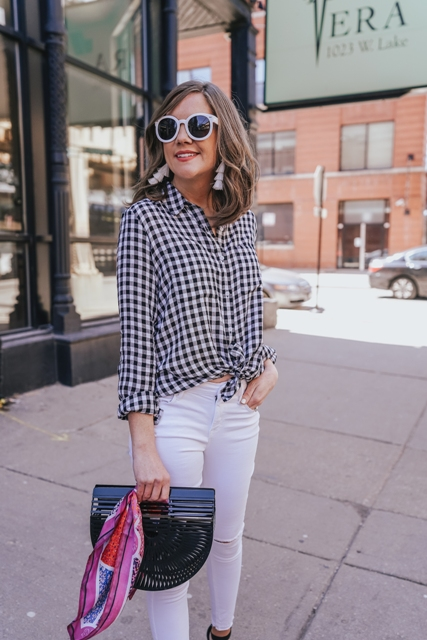 With white skinny pants, rounded sunglasses, black bag and high heels