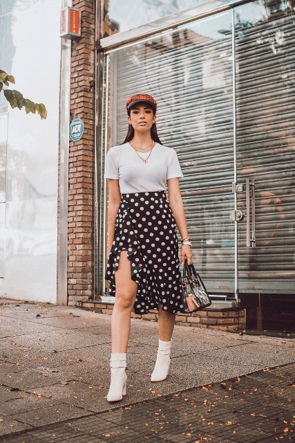 With white t-shirt, bag, white ankle boots and checked cap