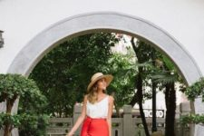 With wide brim hat, white top, beige tote bag and black ankle strap shoes