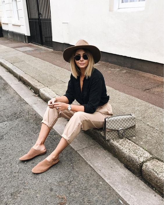 a black button down, tan cropped pants, a camel hat, camel slipper mules and a comfy bag