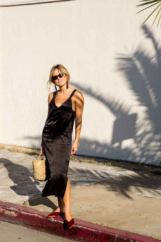 a black silk slip dress with side slits, a straw bag and deep red pointed toe slipper mules