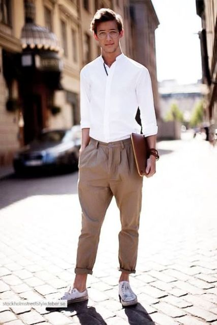 a casual work outfit with a white button down, tan pants, white sneakers and a leather file