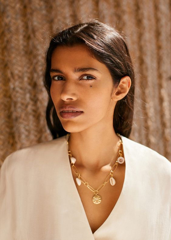 a chic statement necklace in gold with seashells and a pendant in the center is a cool idea for every day