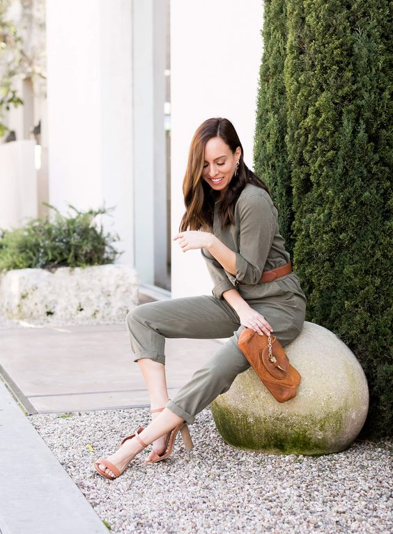 a grey boiler suit styled with a brown belt, clutch and block heels for a party or work