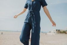 a navy boiler suit with cropped pants, short sleeves and a row of buttons plus white sneakers for summer