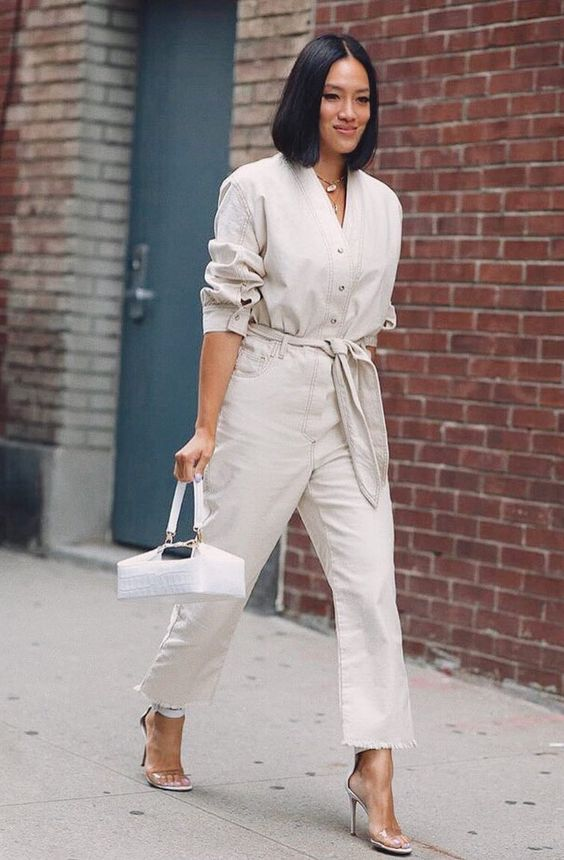 a neutral boiler suit with a sash, buttons and a raw hem, acrylic heels and a catchy white bag