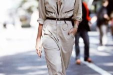 a neutral boiler suit with black touches and a black belt, white mules and sunglasses