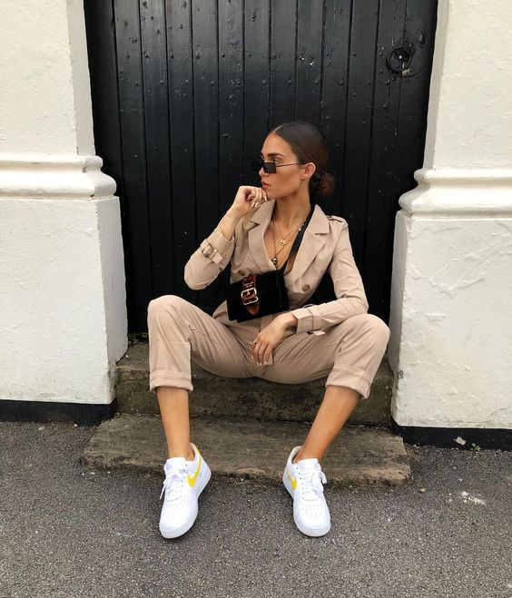 a nude boiler suit with cropped pants, buttons, white sneakers and a small black crossbody