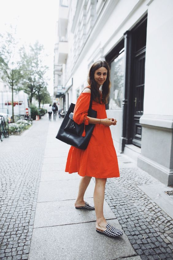 a red off the shoulder A-line knee dress, checked slipper mules and a black tote