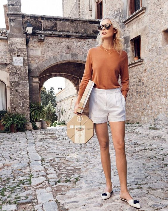 a casual summer look with a rust long sleeve top, white shorts, white tassel mules for a girlish feel in the outfit