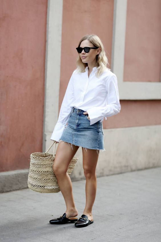 a white button down, a blue decomposed denim mini, black slipper mules, a straw bag