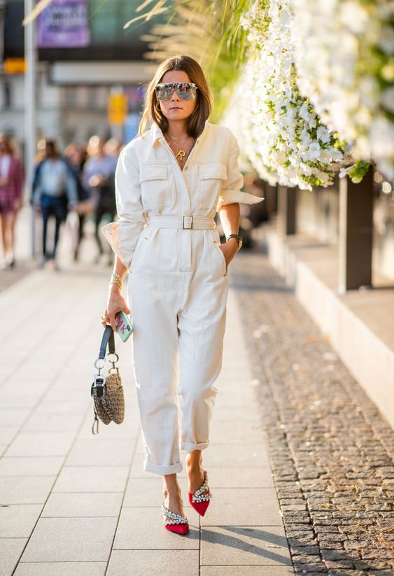 a white denim boiler suit with wide sleeves, catchy embellished red shoes and a small straw bag