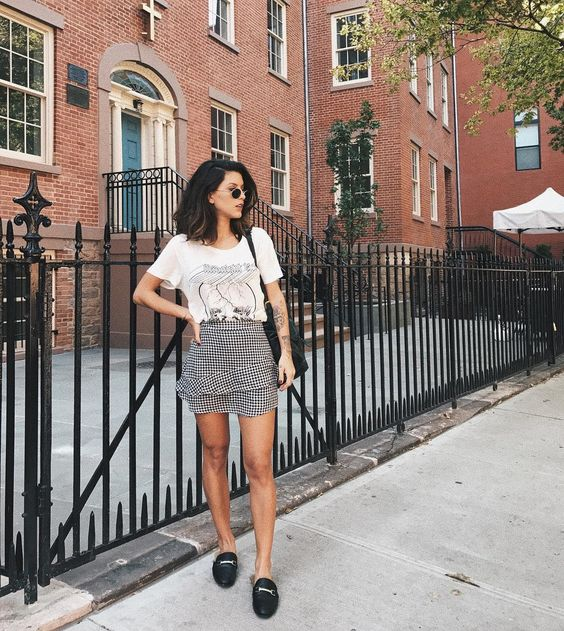 a white printed tee, a checked mini skirt with a catchy detail, black mules and a black bag