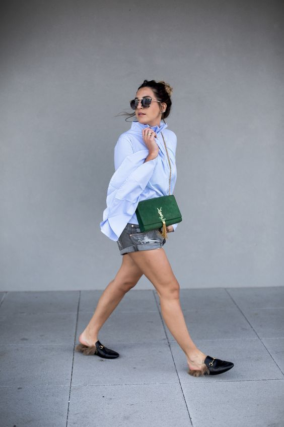 an oversized blue button down, decomposed denim shorts, black slipper mules and a green bag