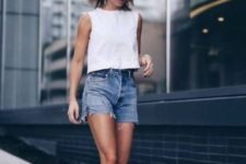 blue distressed denim shorts, a white sleeveless crop top and black slipper mules will keep you cool in every sense on a hot summer day