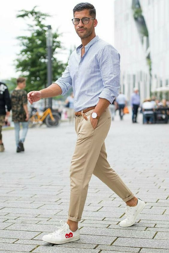 tan pants, a blue striped button down, white sneakers and a brown belt to stay cool in summer