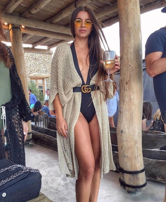 a black one piece swimsuit with a plunging neckline and a crochet coverup with a belt plus sunglasses