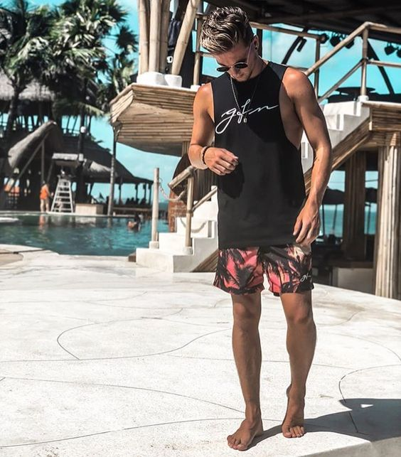 a black sleeveless printed tee and bright palm print shorts to go to the beach
