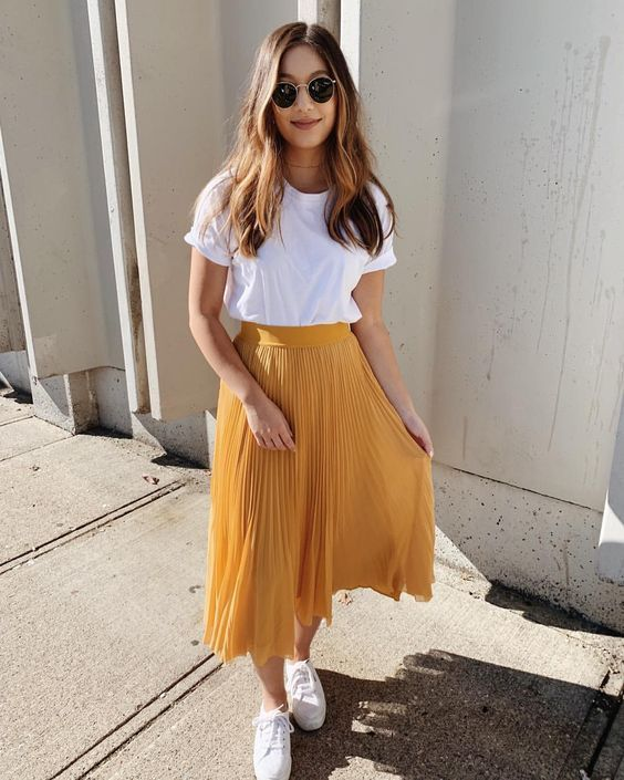 a white basic tee, a marigold pleated midi skirt, white sneakers compose a simple summer look