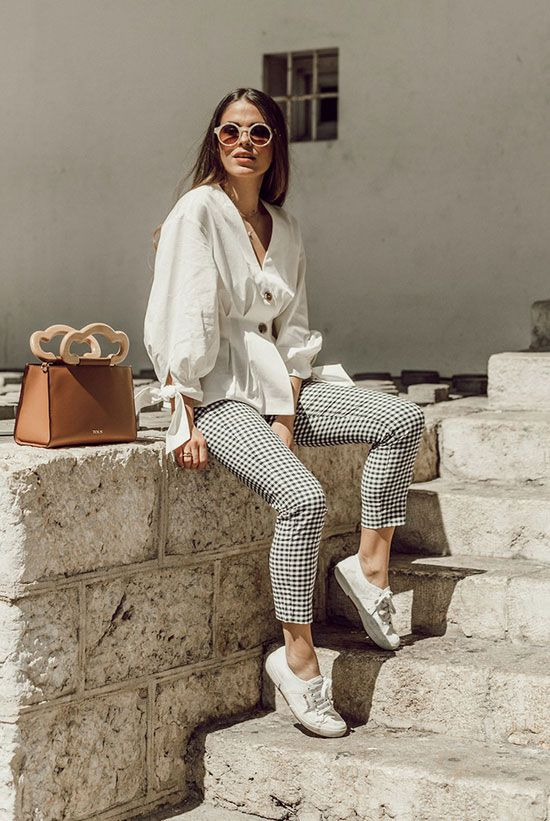a white blouse with buttons and tied sleeves, plaid cropped pants, white canas sneakers and a camel bag