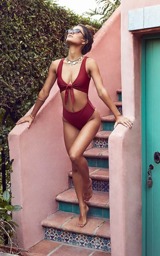 a burgundy thick strap one piece swimsuit with a cutout front and a knot top