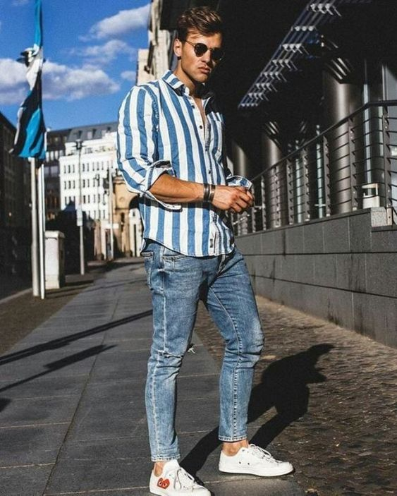 a relaxed summer outfit with a striped blue and white shirt, blue jeans, white sneakers
