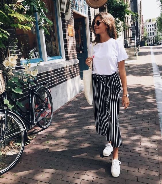 a white basic tee, striped high waisted pants, white canvas sneakers and a large tote