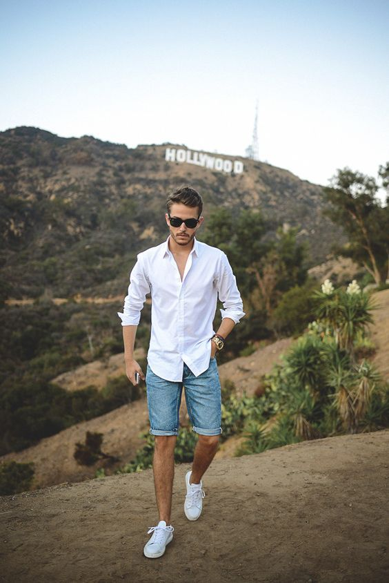 a white shirt with rolled up sleeves, denim shorts and white sneakers for a hotter day