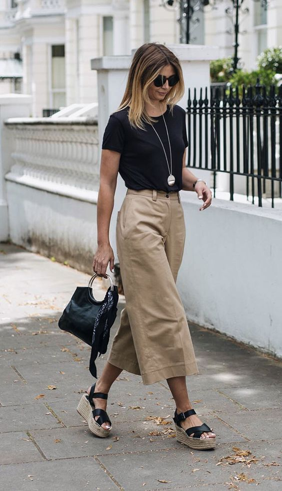 a black teee, camel culottes, black wedges and a black bag for a casual look with a touch of elegance
