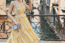 04 a bright striped yellow and white midi ruffle dress with spaghetti straps, black heels and a grey bag